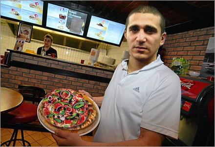 Ismail Mahmallah visar upp sin skapelse pizza-pizzan,